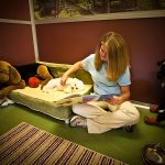 Staff member reading to a dog in a Morris Animal Inn Luxury Suite